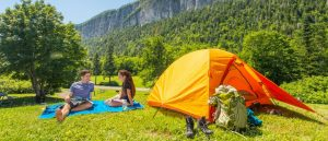 Couple camping at a scenic place with mountain backdrop