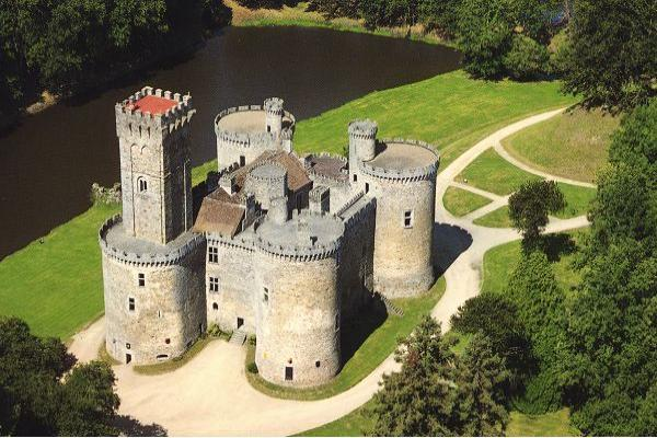 Top View Of A Castle Like Designed Building Surrounded By Water Body And Greenery