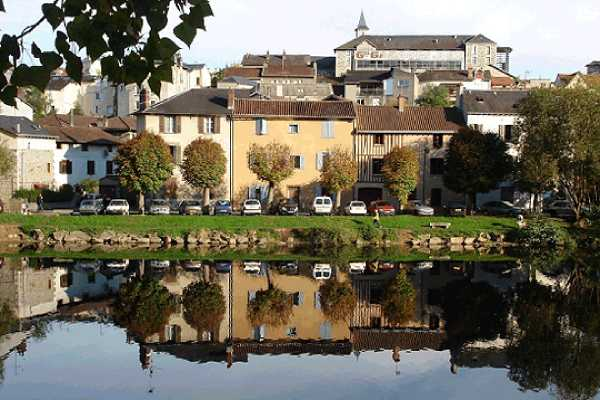 Buildings And Houses With Cars Parked In Front And The Same Picturesque Can Be Seen As A Mirror Image In Water