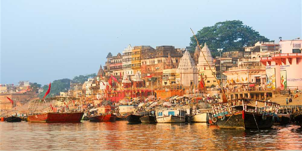 Flotilla Of Boats At The Ghats In Varanasi, Enhance The Ganges Riverfront With A Multitude Of Shrines, Temples, And Palaces.